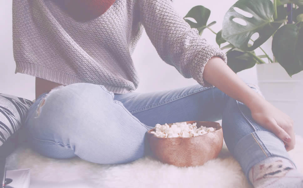 A girl sitting with comfy clothes, in a relaxing environment and eats popcorn