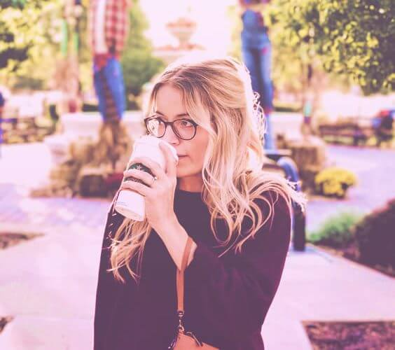 blonde woman with glasses walking in a park