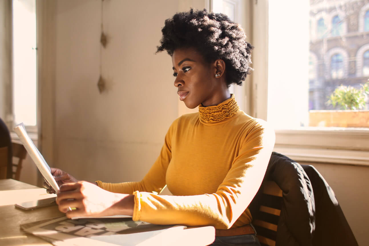 beautiful black woman reading a newspaper as part of her good habits
