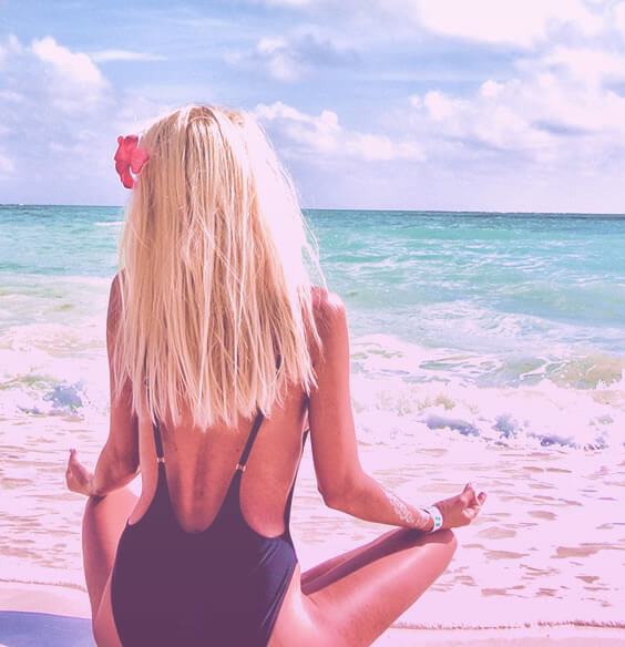 woman meditating on the beach as part of her mindfulness activities
