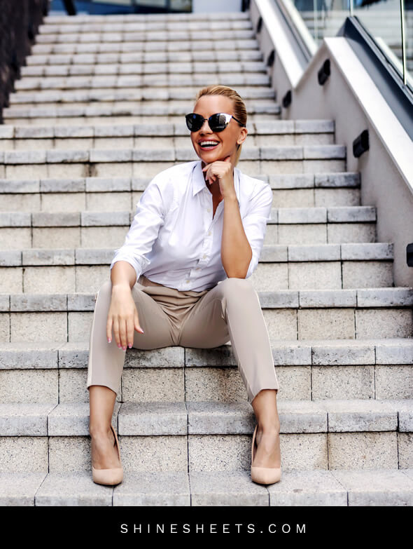 smart-looking woman laughs on stairs outside after personality development tips implementation