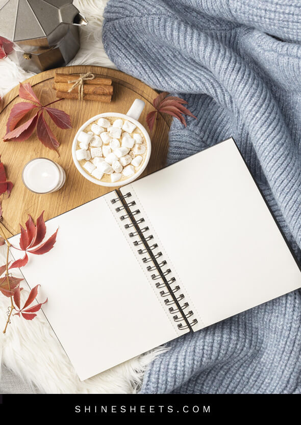 journal for therapy, cup of cocoa and fall leaves on the bed