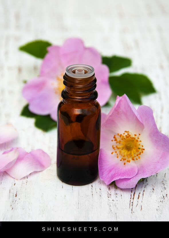a small bottle of rosehip oil for face and rosehip flowers