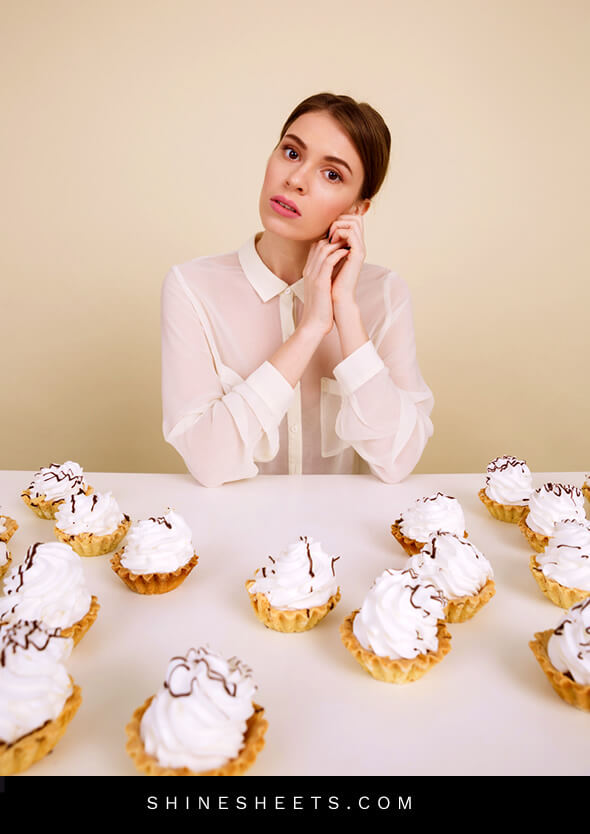 woman sitting in front of the cupcakes trying to stop binge eating