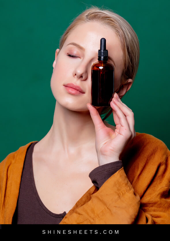 woman with closed eyes and rosehip oil for face