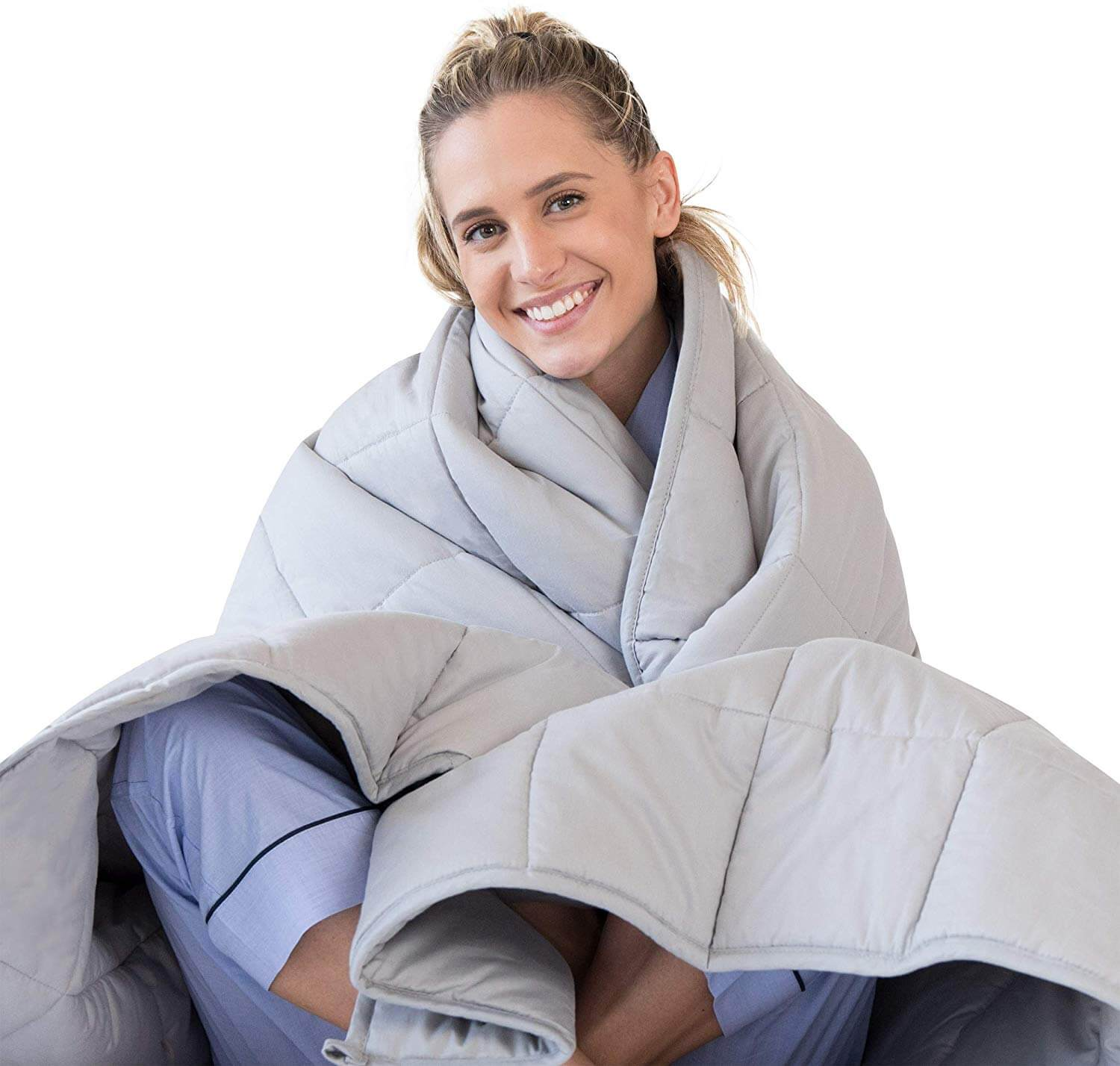 A young blond woman sits under weighted blanket