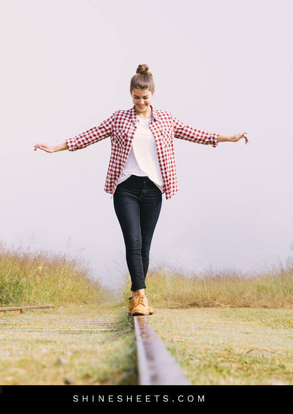 happy woman walking on railtrack as a concept of living happier with life balance