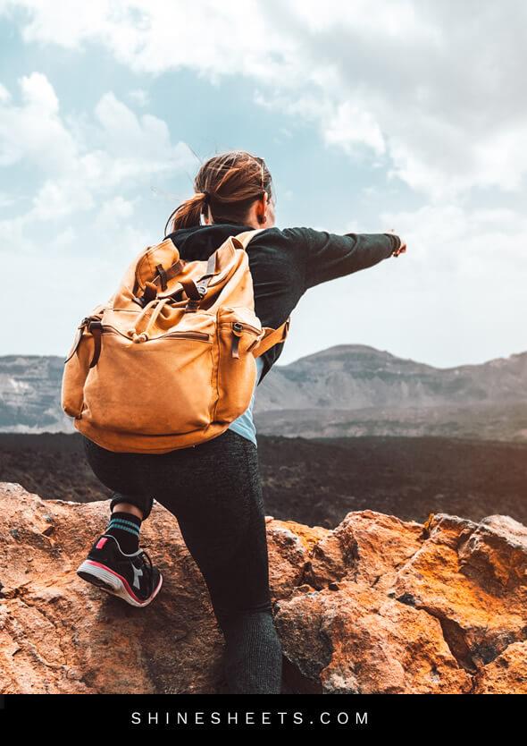 woman climbing a mountain as a symbol of living happier through adventure