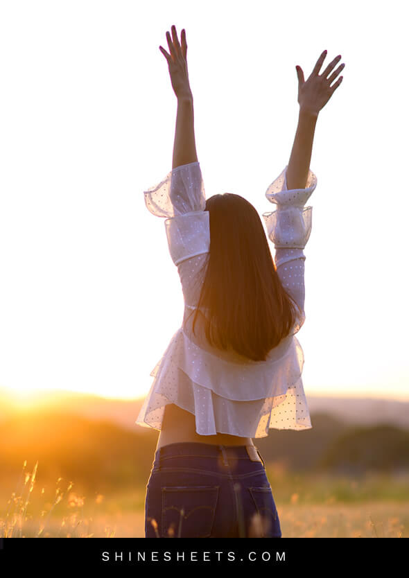 woman with her hands in the air as a symbol of living happier