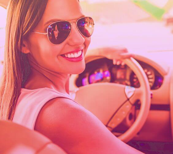 Woman with sunglasses holds the wheel and smiles in a very organized luxurious car