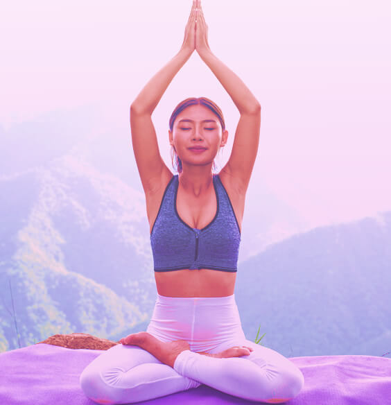 Youn asian female in yoga pose sitting on a mountain and meditating