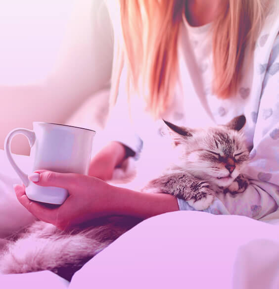 Young woman in her pyjamas holds her cat and a white cup
