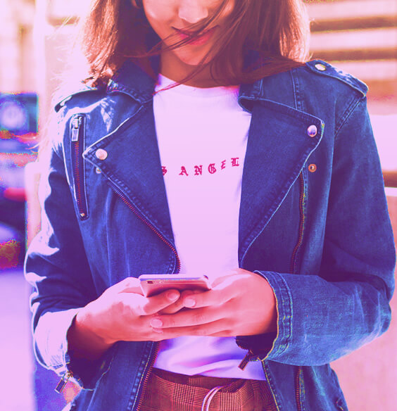 A girl holds phone and smiles while writing a text message
