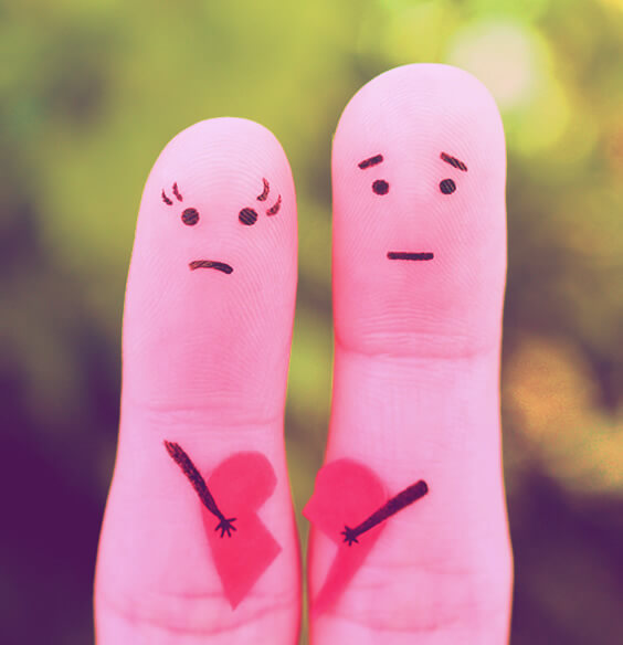 Two fingers painted like an unhappy couple holding a broken heart