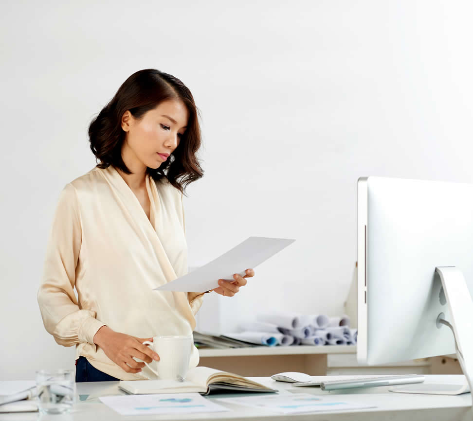 Young asian woman near computer showing singletasking as one of success habits