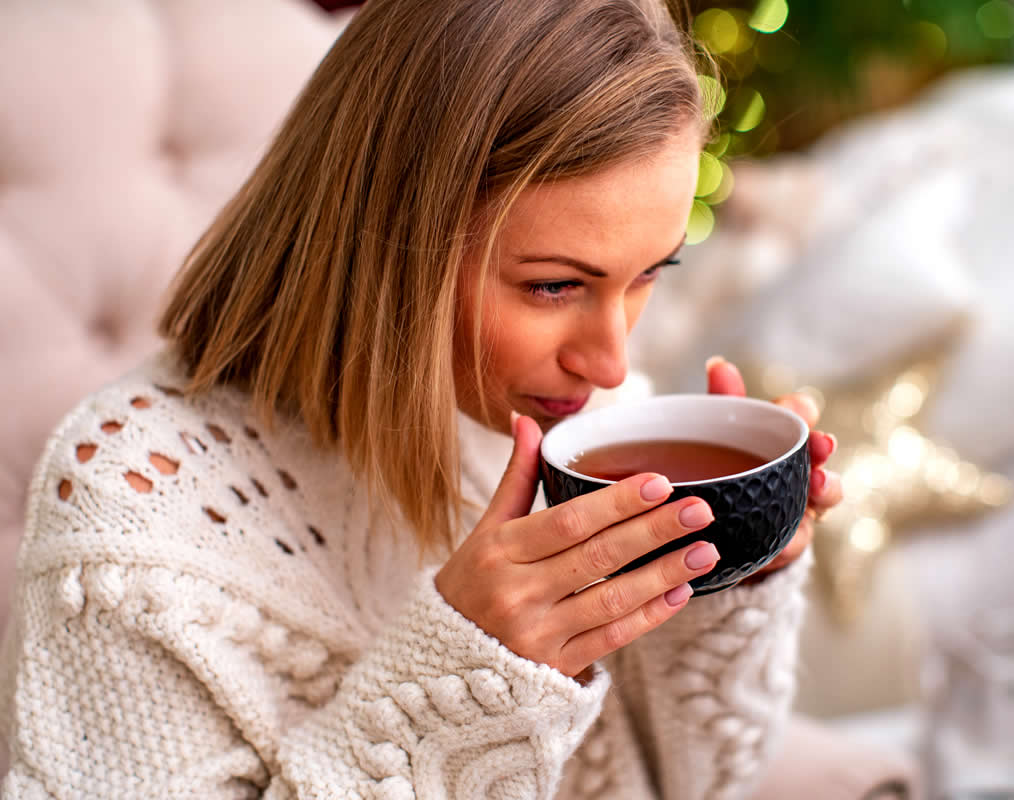 Woman drinking tea and taking self care as part of her success habits