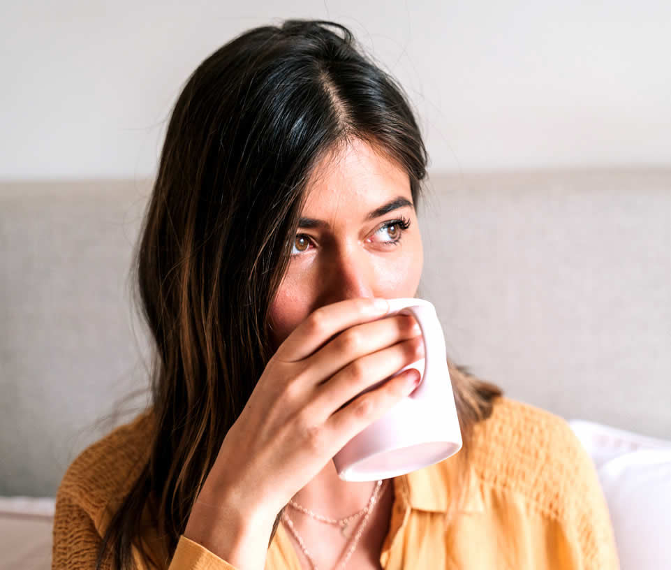 Woman is having health anxiety and is drinking tea from a pink cup
