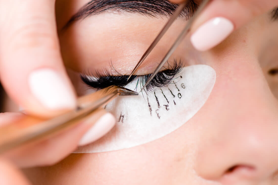 Woman getting eyelash extensions close up