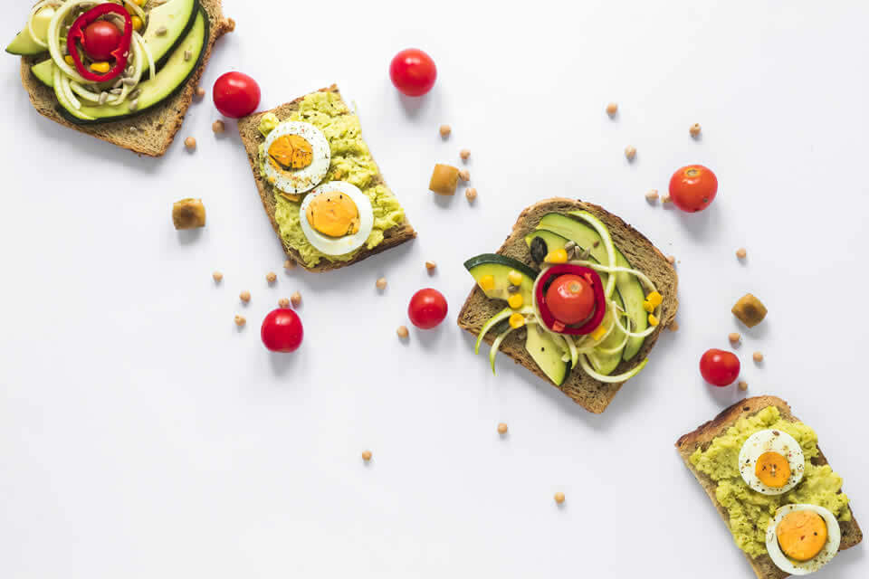 Healthy breakfast example of sandwiches with avocado, eggs and vegetables
