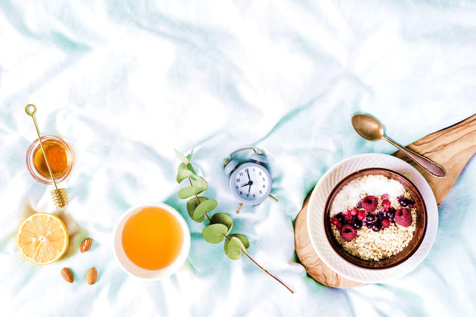 Fruits, nuts, oatmeals and a clock as an ilustration of intermittent fasting