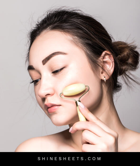 woman using jade roller to massage her face after reading beauty tips for face