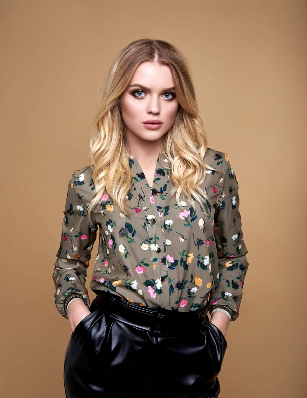 Blonde woman with leather pants and silk pants shows an example of personal style