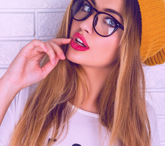 woman with glasses shows how to make your face slimmer with facial excercises