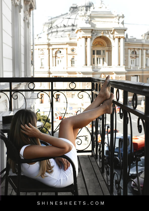 woman sitting risky in a balcony with a white dress