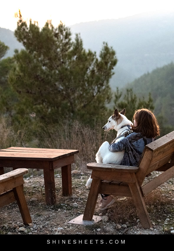woman sitting with her dog on a mountain to find inner happiness