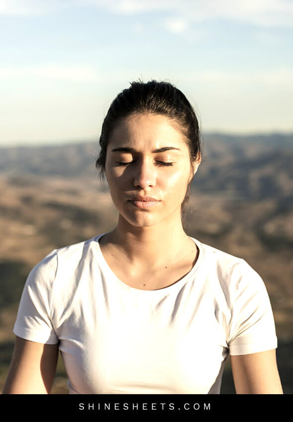 woman meditating on a mountain to find inner happiness