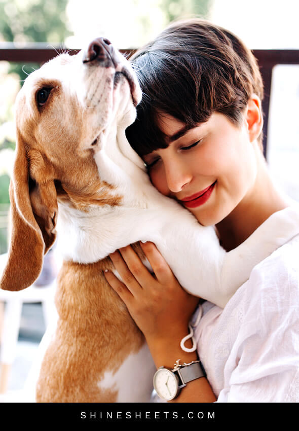 happy woman smiling hugging her dog