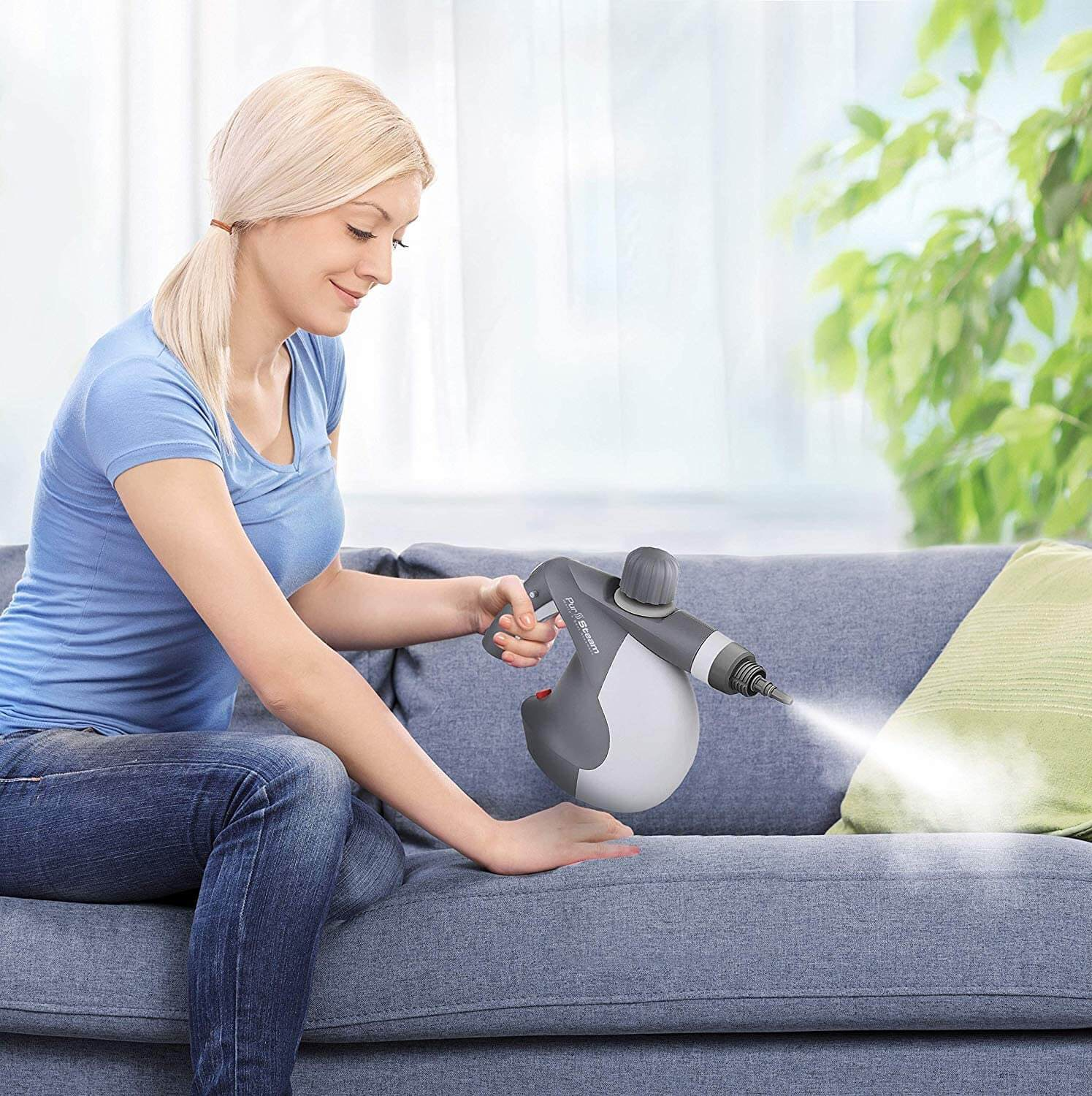 Young blonde woman using steam cleaner to clean sofa