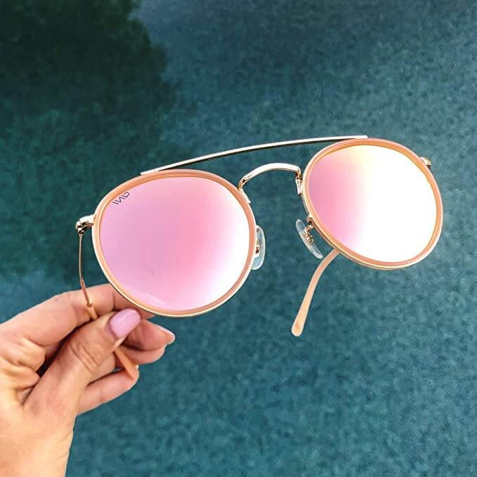 Woman with pink nails hols pink sunglasses