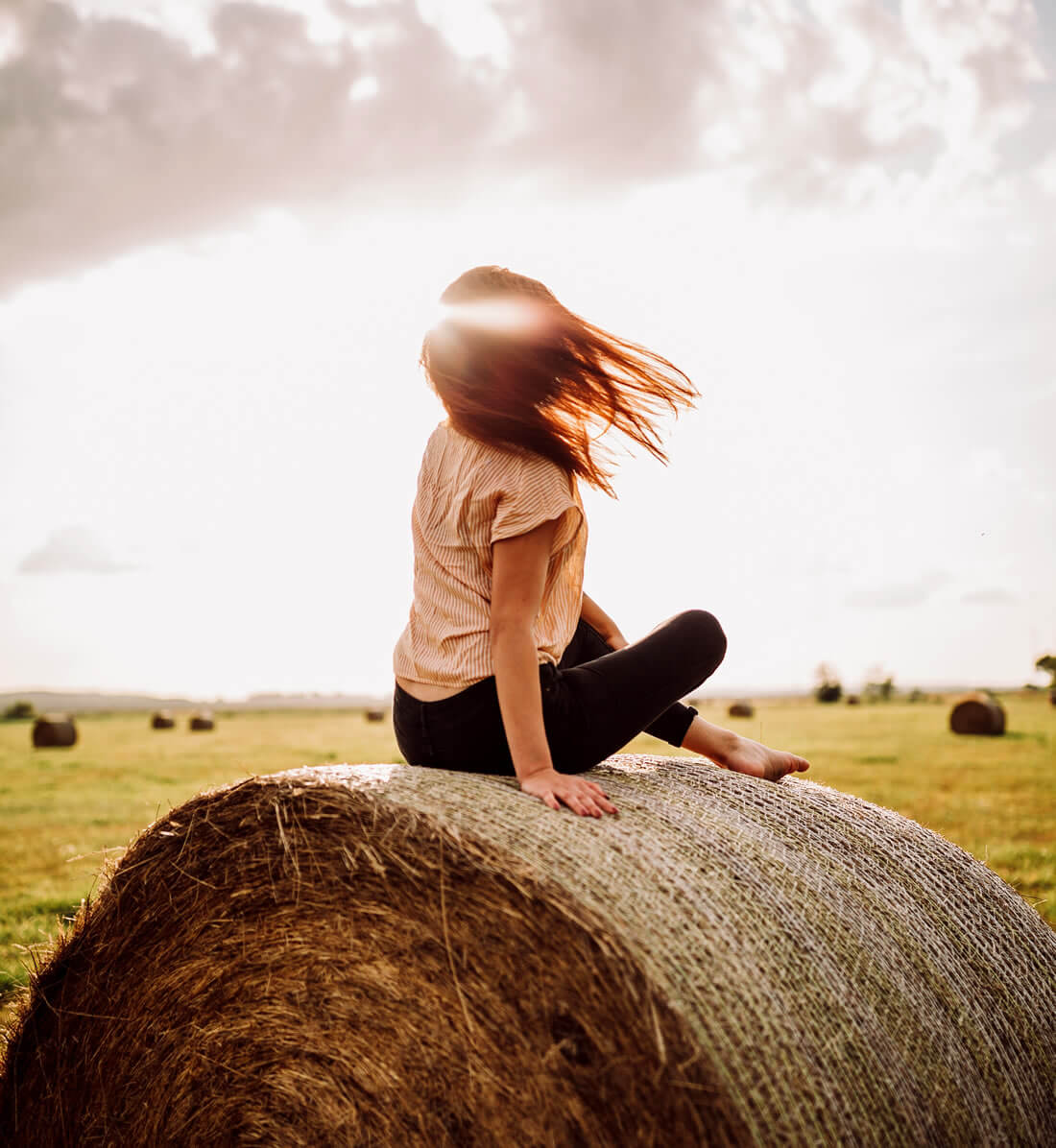 Woman sitting in the nature on hay stack to practice self love