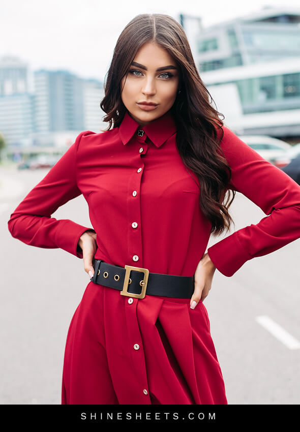 confident woman in a red dress as an illustration of how to be a lady