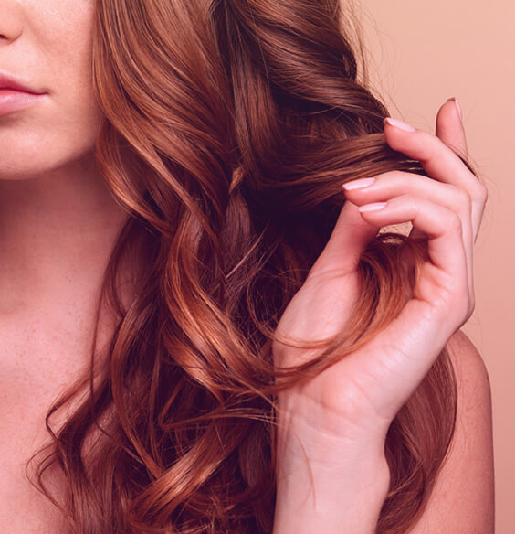 young woman touching her red hair to stop hair loss