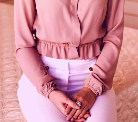 woman in pretty ruffled blush blouse showing her dressing sense