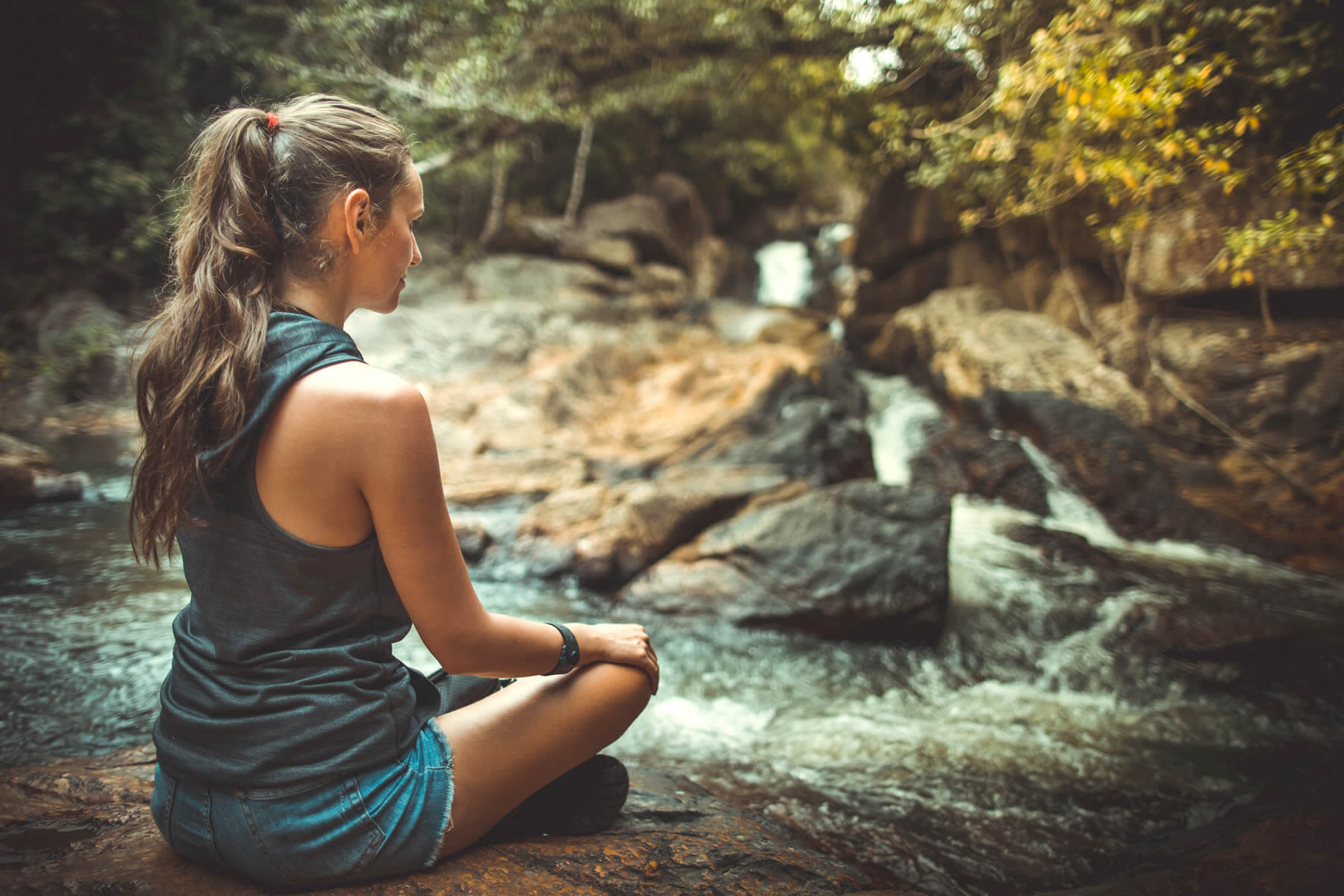 Woman sitting in near a stream to overcome anxiety