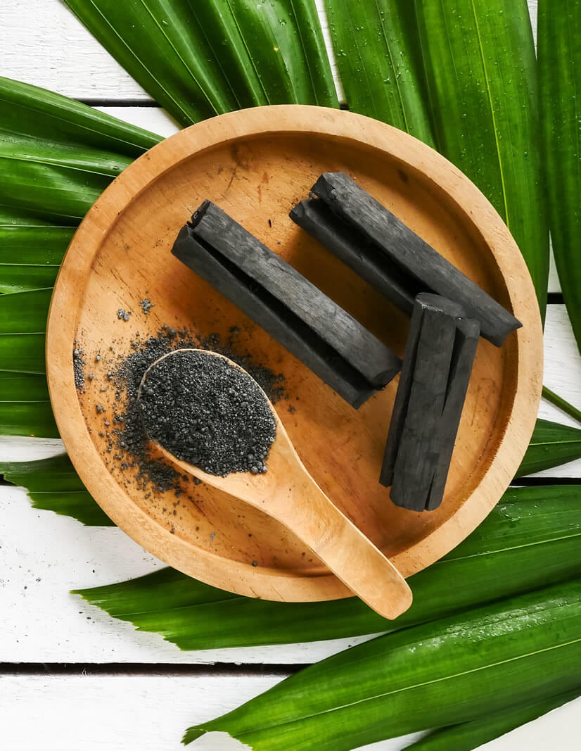 activated charcoal crushed on bamboo table as teeth whitening home remedies