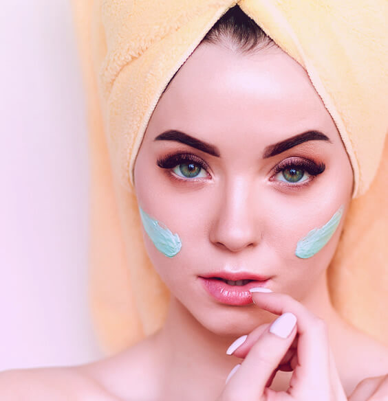young woman using face pack on her skin