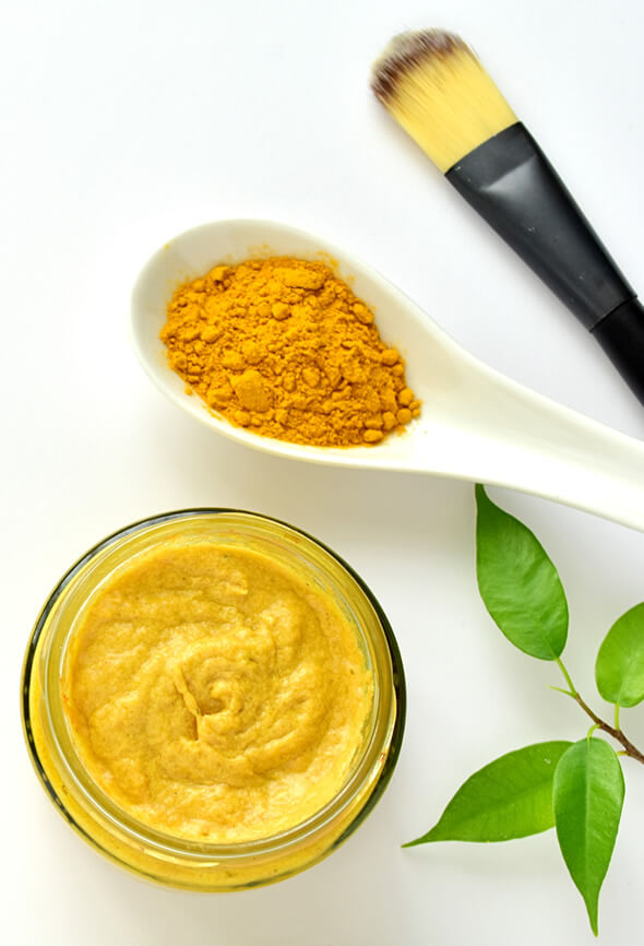 homemade turmeric face pack and a brush on the table