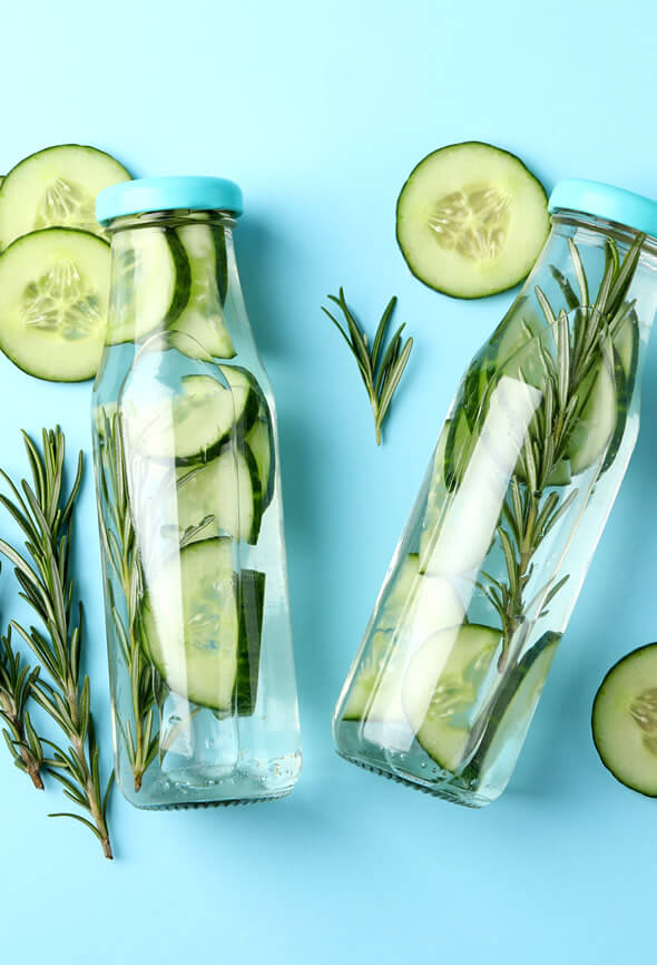 Cucumber infused water bottles with rosemary as one of the wellness tips