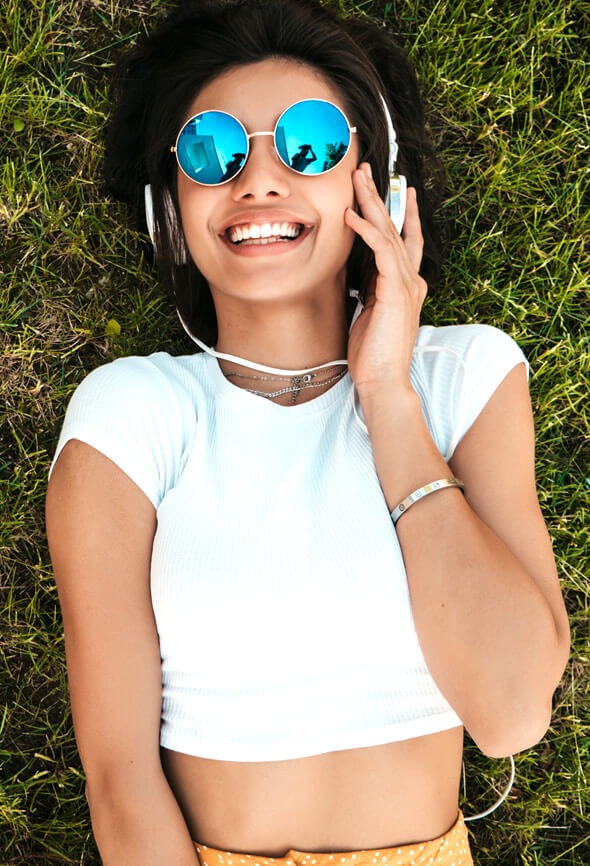 optimistic girl laying on the grass and listening to music
