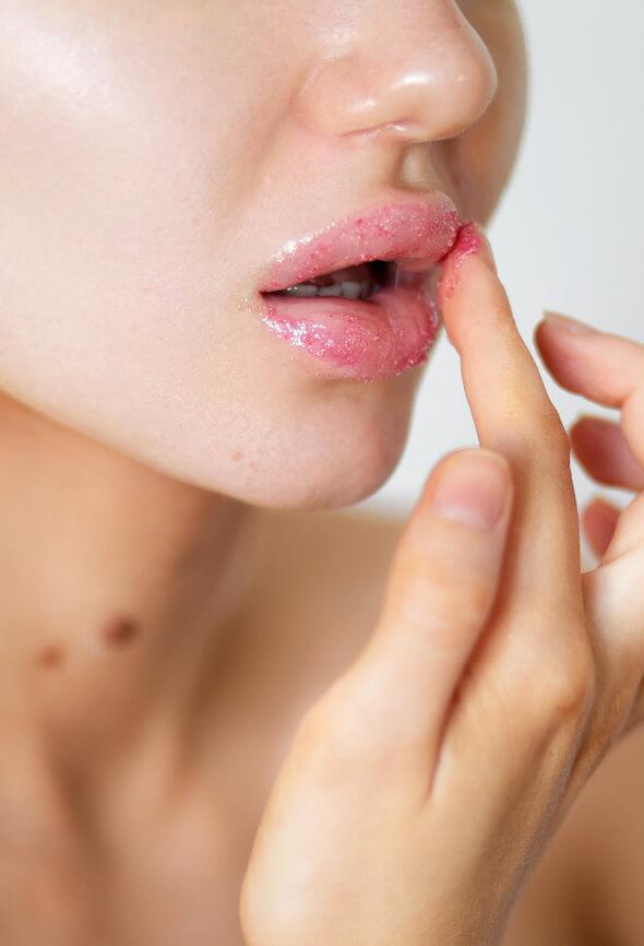 woman using lip scrubs on her lips