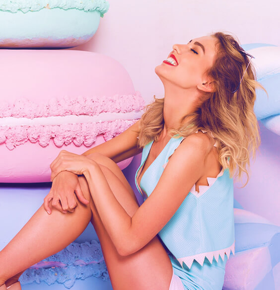 young blonde girl smiling with pastel pillows around