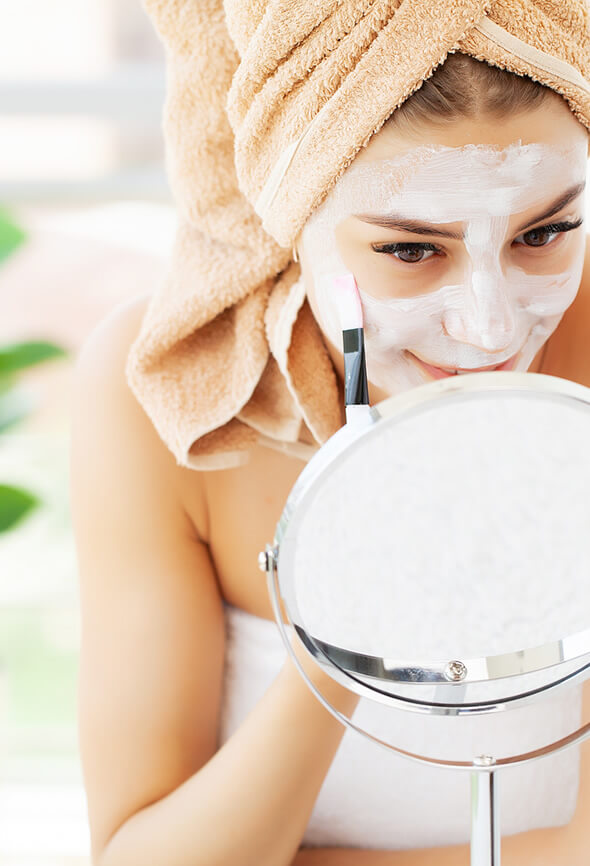 woman applying face pack on her face