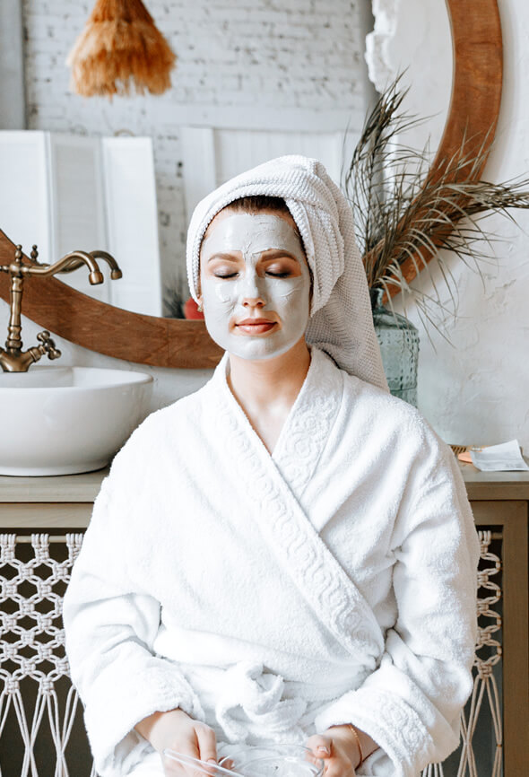woman in the bathroom sitting with a face pack on