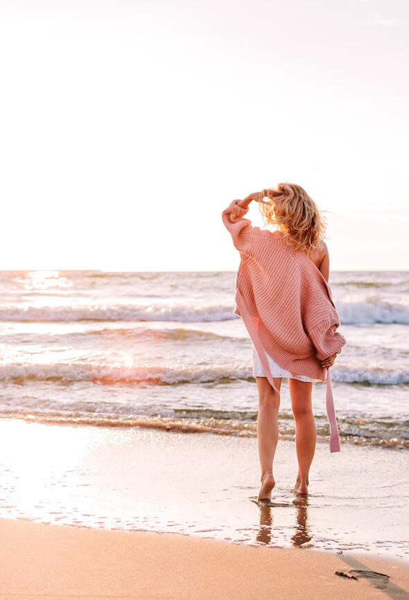 woman walking by the sea to feel better
