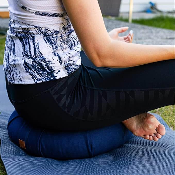 Woman sitting cross-legged on a meditation cushion
