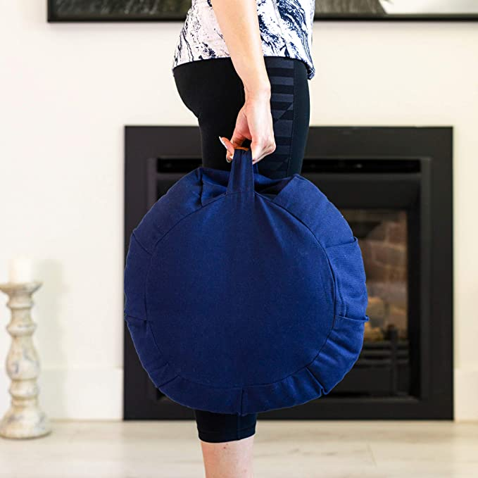 Woman carrying a meditation cushion in her hand